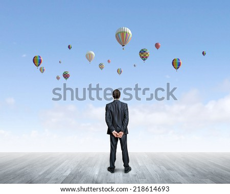 Rear view of hopeful businessman looking at balloons flying in sky - stock photo