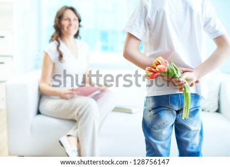 Rear view of lad with bunch of beautiful tulips behind back preparing nice surprise for his mother - stock photo
