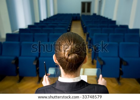 Rear view of lecturer?s head in front of rows of armchairs in conference hall - stock photo