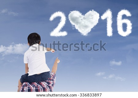 Rear view of little boy and his father looking and pointing at cloud shaped numbers 2016 - stock photo