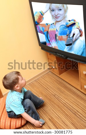 Rear view of little boy sitting on the floor and watching cinema  on TV at home - stock photo