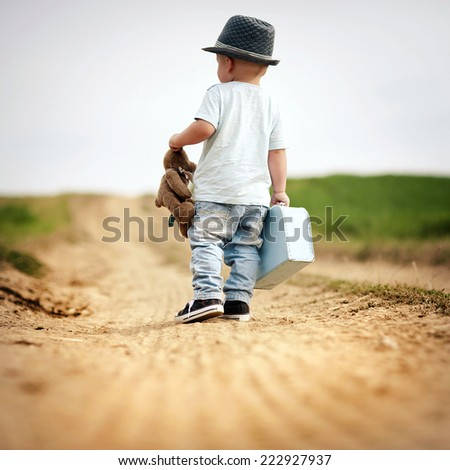 Rear view of little boy walking on the footpath in field with suitacase and teddy bear - stock photo