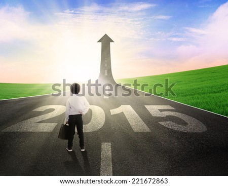 Rear view of little business person standing on the road to future 2015 - stock photo