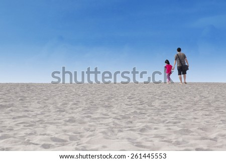 Rear view of little girl and her father walking on the sand dune - stock photo
