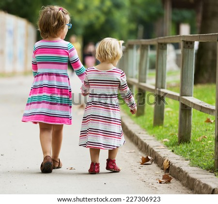 Rear view of  little girls at street in summer - stock photo