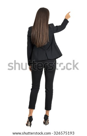 Rear view of long dark hair beauty pointing or presenting on her right side. Full body length portrait isolated over white studio background.  - stock photo