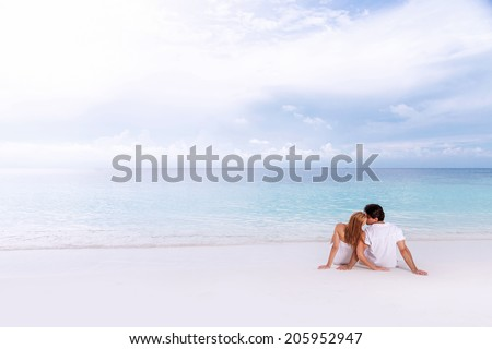 Rear view of loving couple relaxing on the beach, kissing outdoors, boyfriend with girlfriend enjoying summer holidays on luxury Maldives resort, love and romance concept  - stock photo