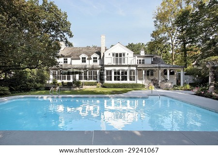 Rear view of luxury home with swimming pool - stock photo