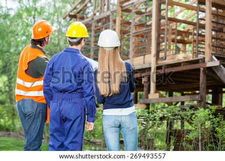 Rear view of male and female engineers examining incomplete wooden cabin at construction site - stock photo