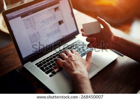 Rear view of male hands holding credit card typing numbers on computer keyboard while sitting at home at the wooden table, soft focus, flare sun light, cross process image - stock photo