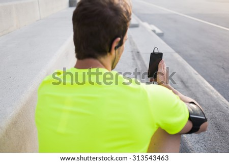 Rear view of male runner browsing internet on his mobile phone while taking break after active intense training outdoors, young sports man use smart phone with blank copy pace screen for text message - stock photo