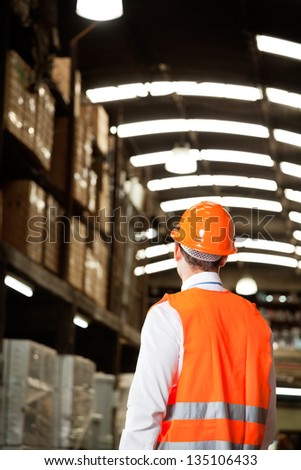 Rear view of male supervisor wearing protective vest and helmet at warehouse - stock photo