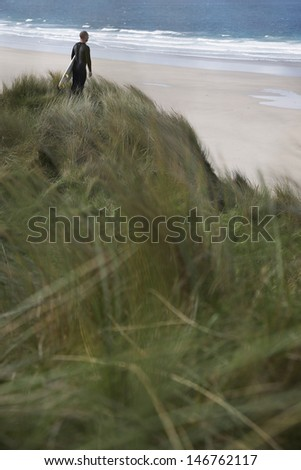 Rear view of male surfer carrying surfboard on beach looking at sea - stock photo