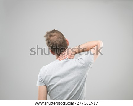 rear view of man experiencing neck pain - stock photo