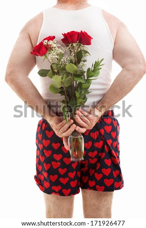 Rear view of man in heart boxers holding a bouquet of flowers behind his back.  White background.   - stock photo