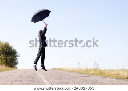Rear view of man jumping with umbrella on the road - stock photo