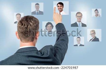 Rear view of man pointing coworkers picture on screen - stock photo