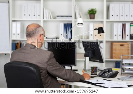 Rear view of mature businessman working at desk in office - stock photo