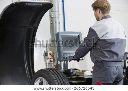 Rear view of mid adult automobile mechanic working in workshop - stock photo