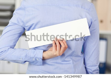 Rear view of mid adult businesswoman holding blank label in office - stock photo