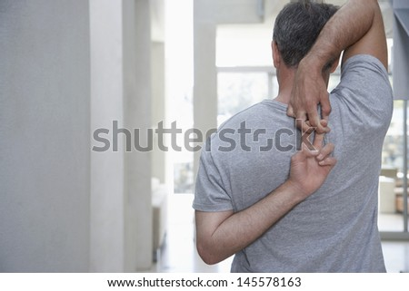 Rear view of middle aged man stretching arms behind back at home - stock photo