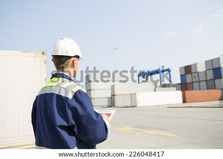 Rear view of middle-aged worker with clipboard in shipping yard - stock photo