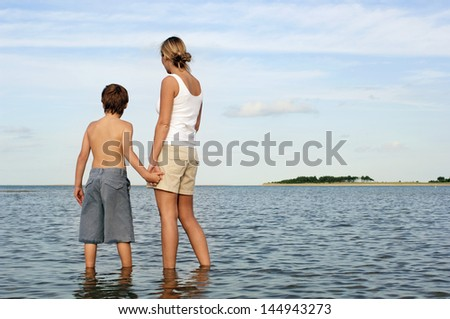 Rear view of mother and son holding hands while enjoying the sea view - stock photo