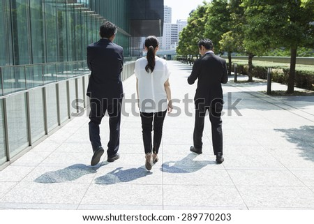 Rear view of multi-ethnic businesspeople walking - stock photo