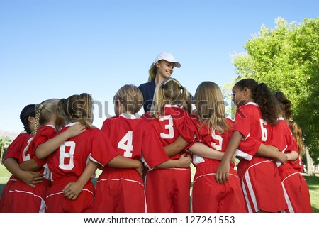 Rear view of multi ethnic football players with coach standing in the front - stock photo