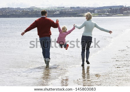 Rear view of parents lifting daughter while walking along beach - stock photo