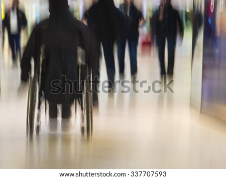 Rear view of person in wheelchair in public place in blurred motion - stock photo