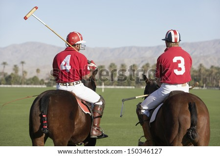 Rear view of polo players holding sticks mounted on horses - stock photo
