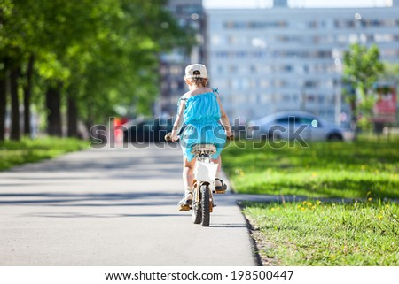 Rear view of pretty girl riding a bicycle in park - stock photo