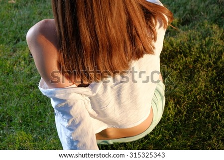 Rear view of redhair teen girl on grass looking away. Back view of redhead teenager girl relaxing alone on grass in summer evening time  - stock photo