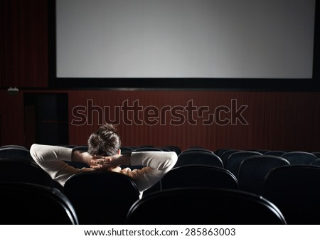 Rear view of relaxed man watching film in cinema theater - stock photo