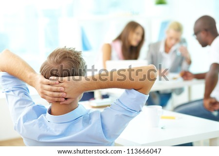 Rear view of relaxed teacher keeping hands behind head and looking at group of students working - stock photo