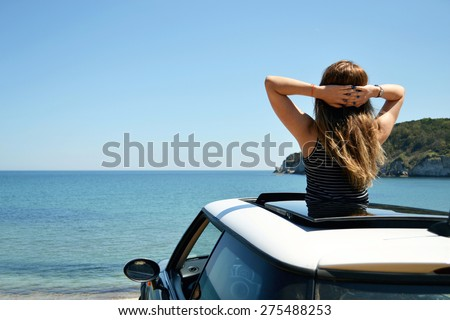 Rear view of relaxed woman on summer travel vacation to the coast leaning out car sunroof towards the sea.  - stock photo