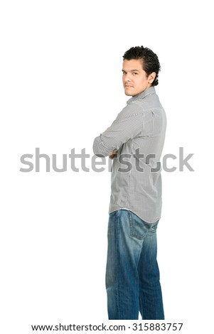 Rear view of reserved hispanic man wearing casual clothes arms crossed looking behind at camera over his shoulder showing facial expression of stern, grave, serious, stoic attitude. Vertical half - stock photo
