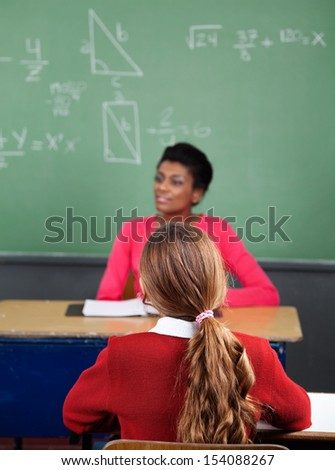 Rear view of schoolgirl sitting at desk with teacher in background - stock photo