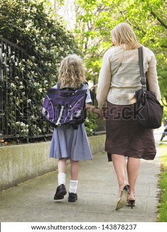 Rear view of schoolgirl walking with mother on pavement - stock photo
