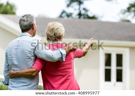 Rear view of senior couple looking at house while standing ih yard - stock photo