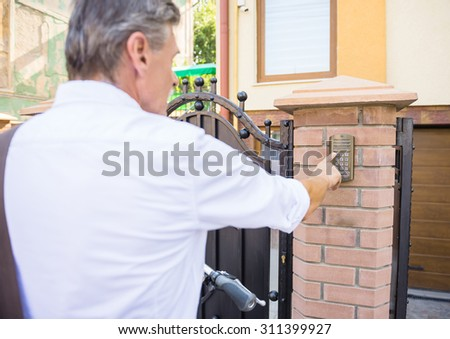 Rear view of senior man is ringing an intercom of an apartment building. - stock photo