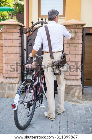 Rear view of senior man with bicycle is ringing an intercom of an apartment building. - stock photo