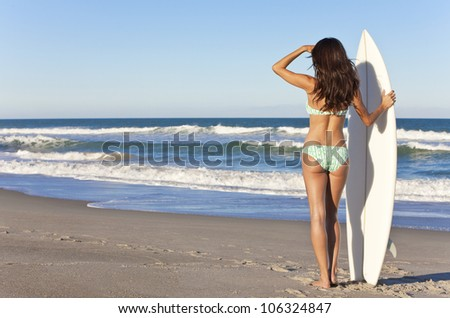 Rear view of sexy beautiful young woman surfer girl in bikini with white surfboard at a beach - stock photo