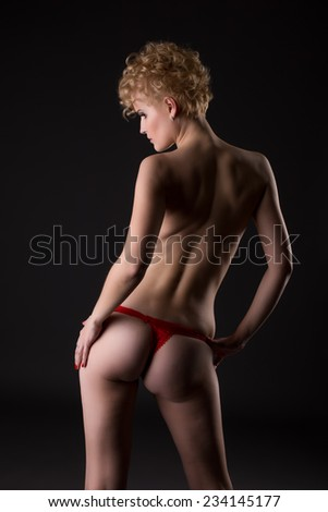 Rear view of slender woman dressed in red thong - stock photo