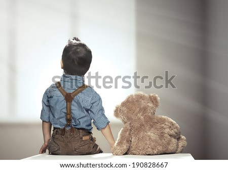 Rear view of small boy with bear  - stock photo