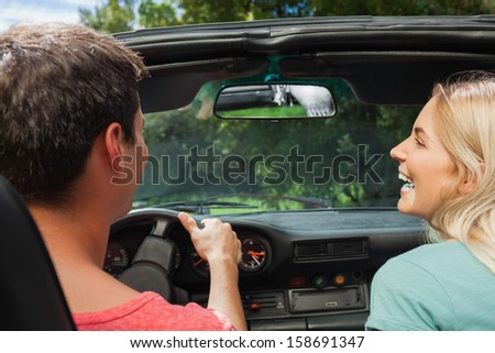 Rear view of smiling couple in cabriolet on a sunny day - stock photo