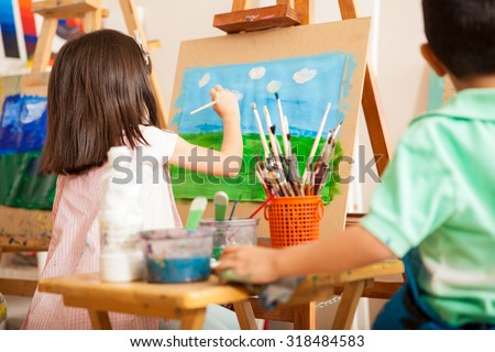 Rear view of some kids working on a painting and drawing some clouds for art class - stock photo