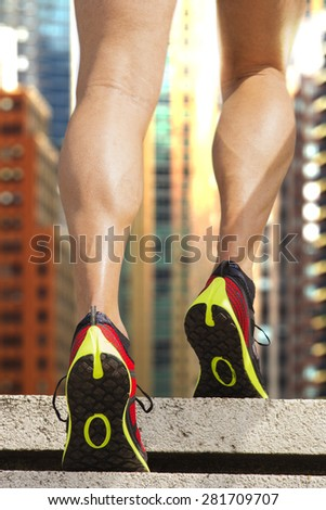 Rear view of stairs climbing athlete with New York building facade  in the background. Strong sun is reflecting on the facade of the background building. - stock photo