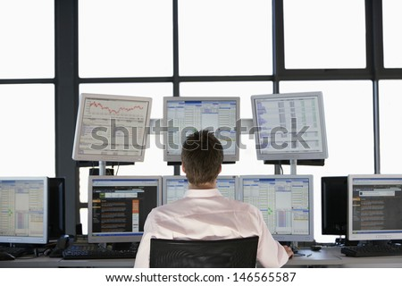 Rear view of stock trader looking at multiple computer screens - stock photo